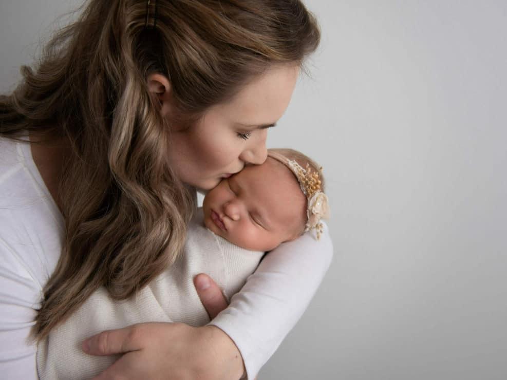 Äiti sukottamassa pientä tyttövauva