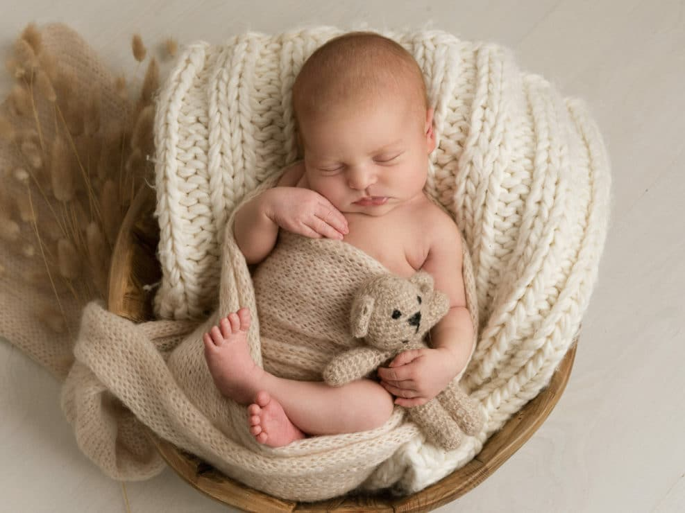 Newborn baby wrapped into brown wrap and holding in hands a teddy bear