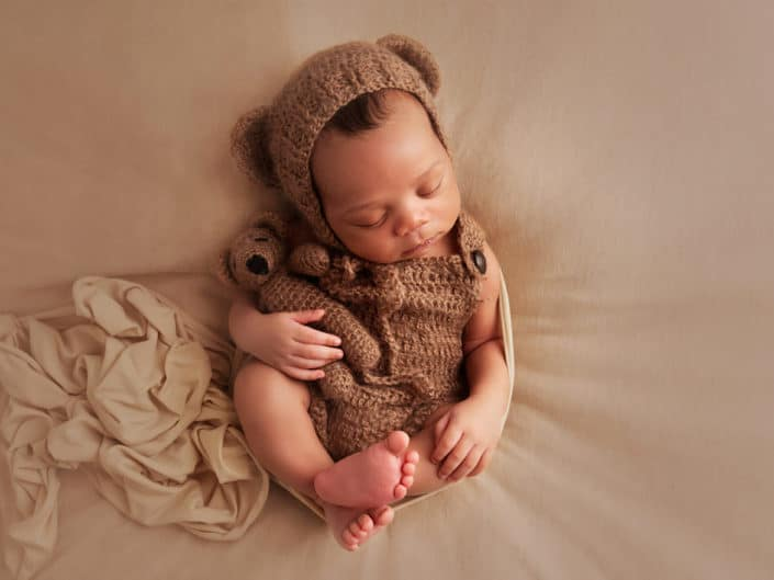 Dark skin newborn boy sleeping in a teddy bear outfit holding in his arms a bear