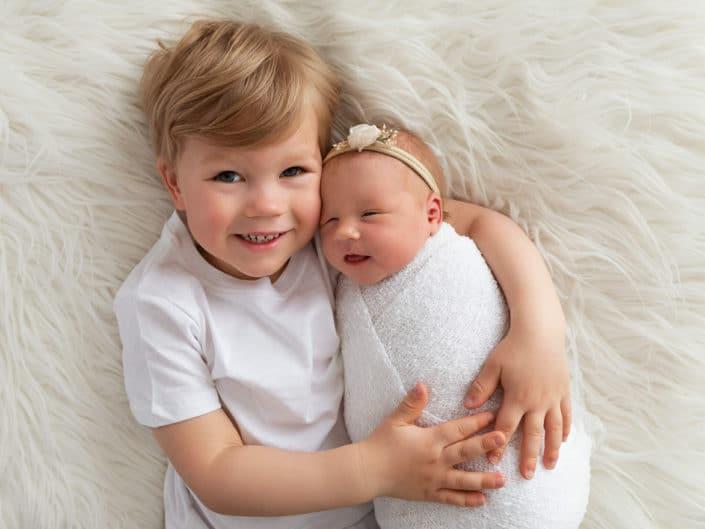 Tyttö vauva valkoisessa kapalossa isoveljen sylissä
