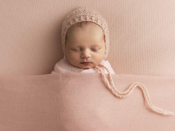 Uninen tyttö vauva vaaleapunaisessa kapalossa ja myssyssä