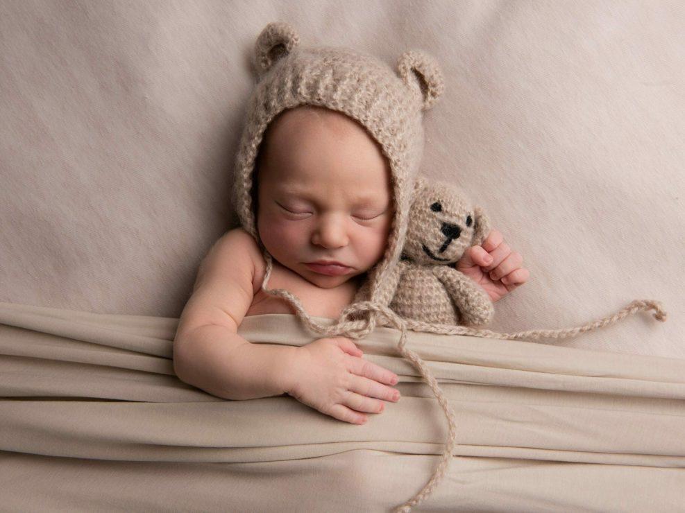 Vastasyntyneen poika vauva peiton alla nalle hatussa ja nallen sylissä