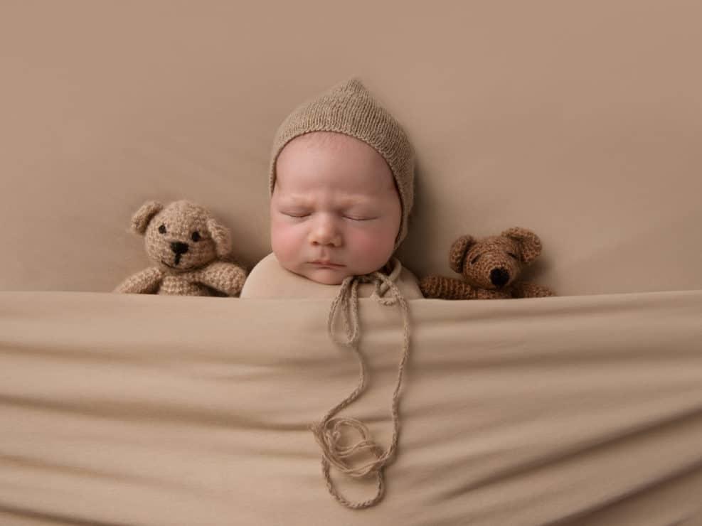 Vastasyntyneen poika vauva ruskeassa kapalossa ja hatussa nallen keskellä