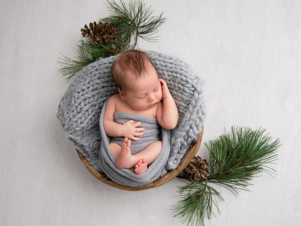 Vastasyntynyt poikavauva harmaassa kapalossa nukkumassa korissa kuusen oksien ympärillä