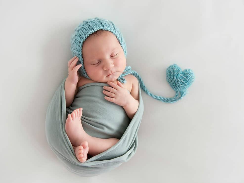 vastasyntynyt poikavauva nukkumassa sinisessä kapalossa ja myssyissä