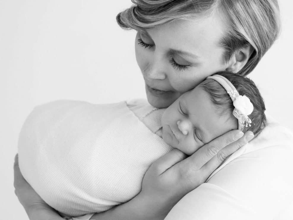 Vastasyntynyt tyttövauva äidin sylissä mustavalkoisessa kuvassa