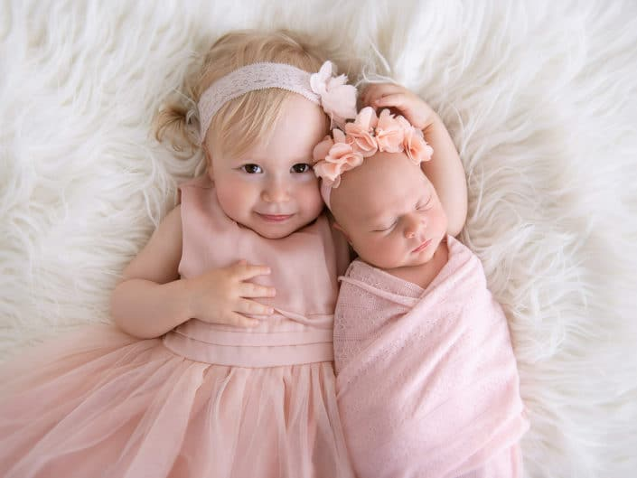 vastasyntynyt vauva nukkumassa siskon sylissä