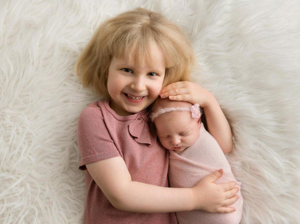 Newborn baby girl sleeping in her sister's arms