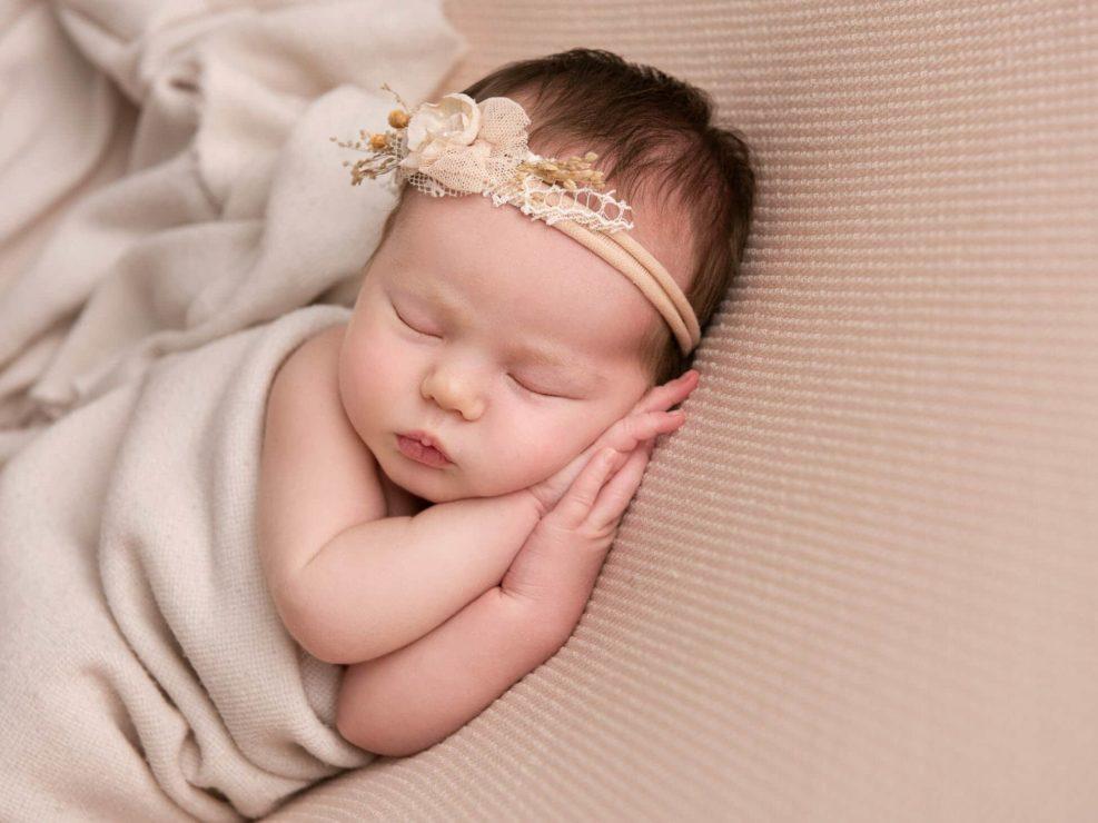 Newborn baby girl sleeping on her left side with hands under her cheek