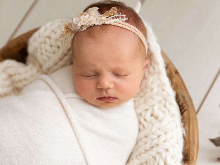 Newborn baby girl wrapped into white cloth sleeping in a bowl
