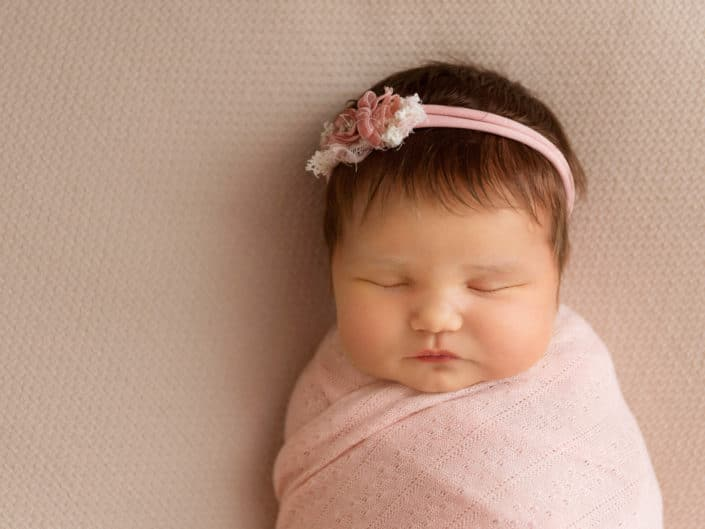 Newborn baby girl in a pink wrap and headband
