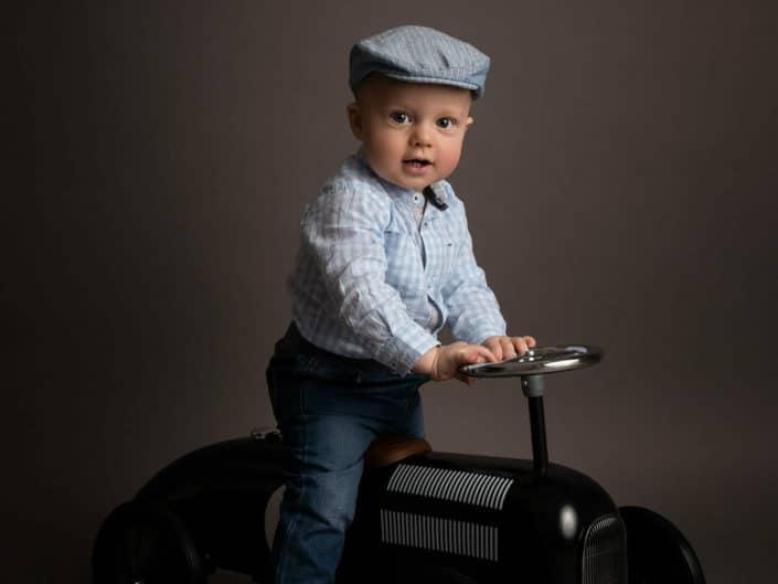 1 vuotias poika istumassa autolelun päällä