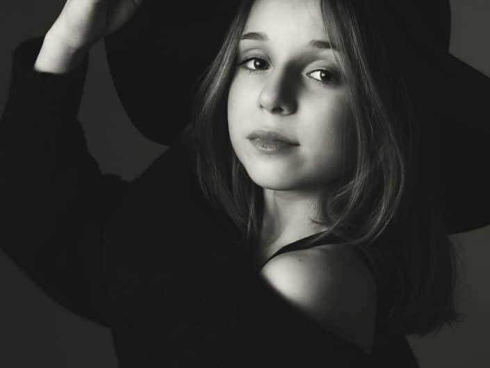 Nuori tyttö mustassa puserossa ja hatun päällä katsomassa suoraan kameraan