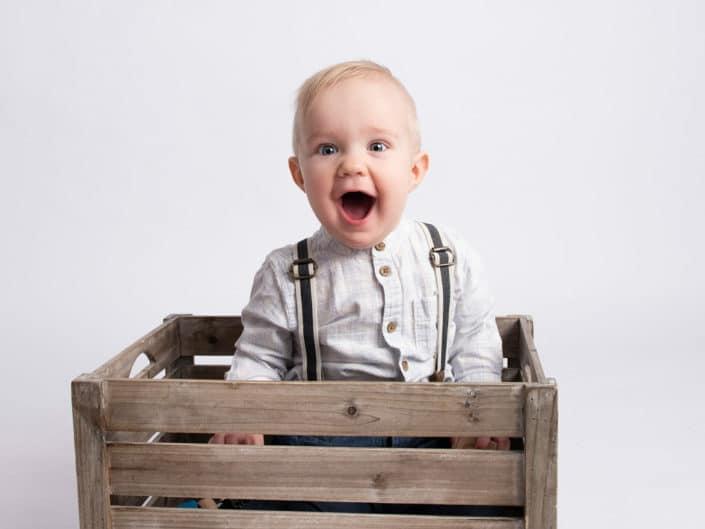 Hymyileva yksi vuotias poika istumassa puuissa laatikossa