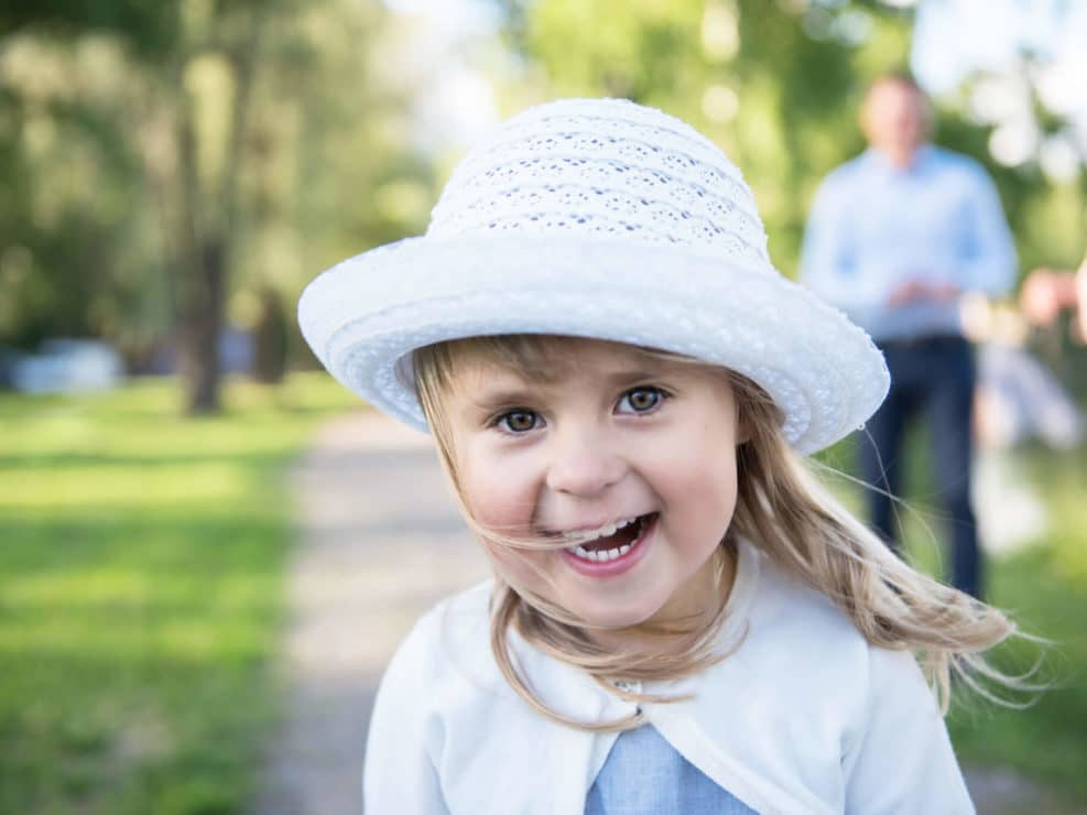 Hymyilevä tyttölapsi puutarhassa