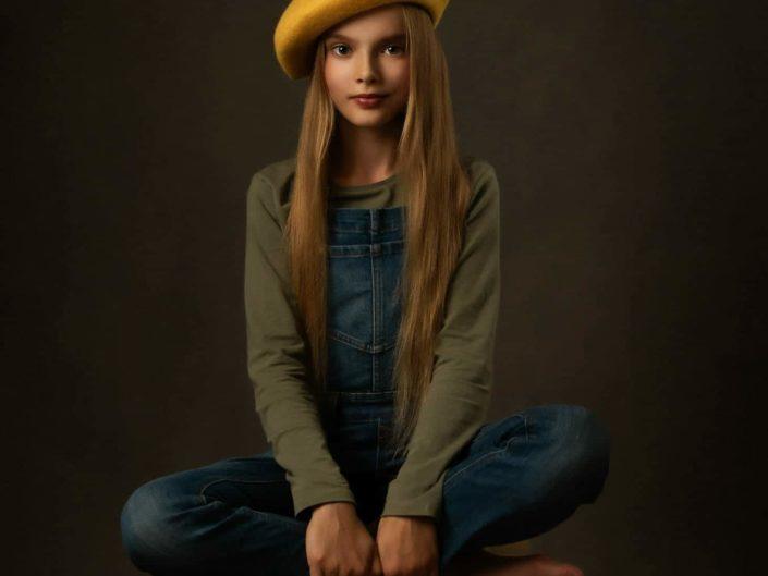 Nuori tyttö keltaisessa hatussa ristissä istumassa