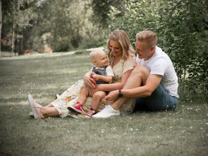 Perhe istumassa puutarhassa ja katsomassa toisiaan