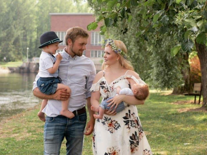Perhe kävelemässä puistossa kesän iltapäivällä