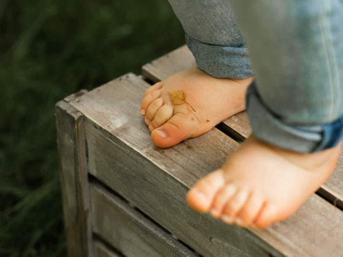 One year old boy toes on a wooden basket