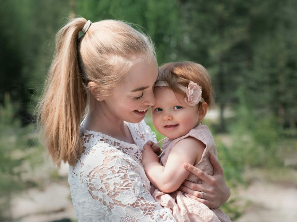 Pieni tyttö äidin sylissä katsomassa kameraan
