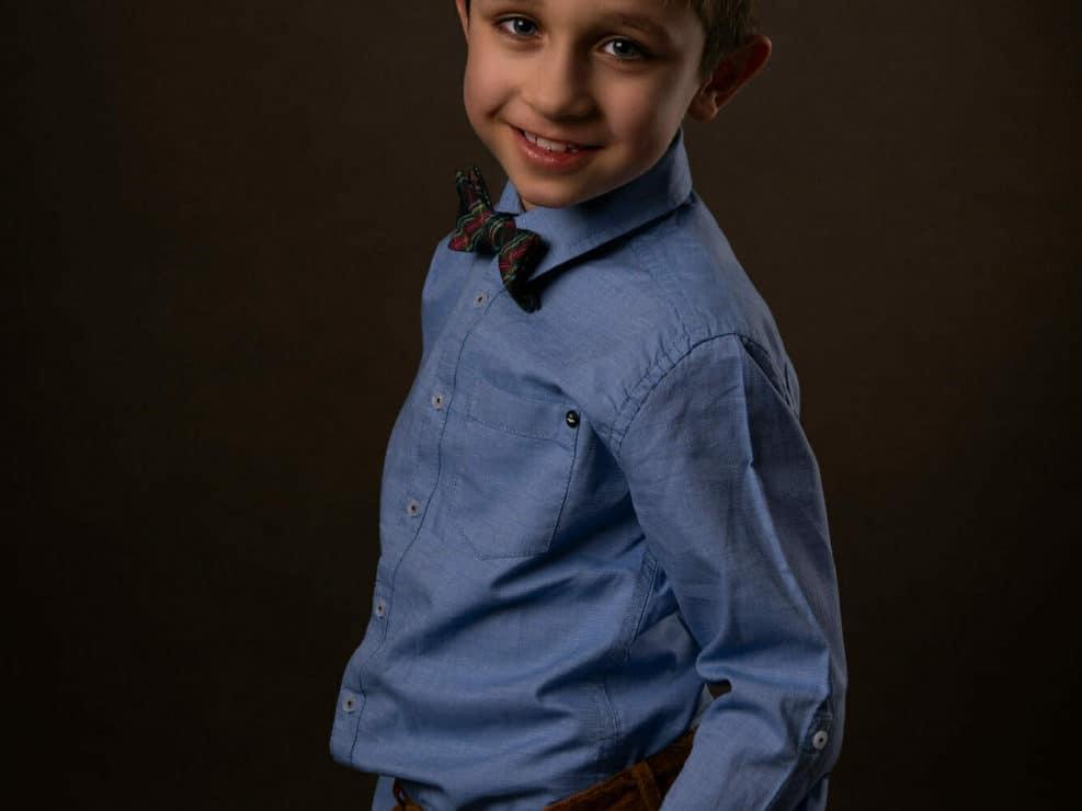 Poika sinisessä paidassa rusetin kanssa ja käsien taskuissa katsomassa suoraan kameraan