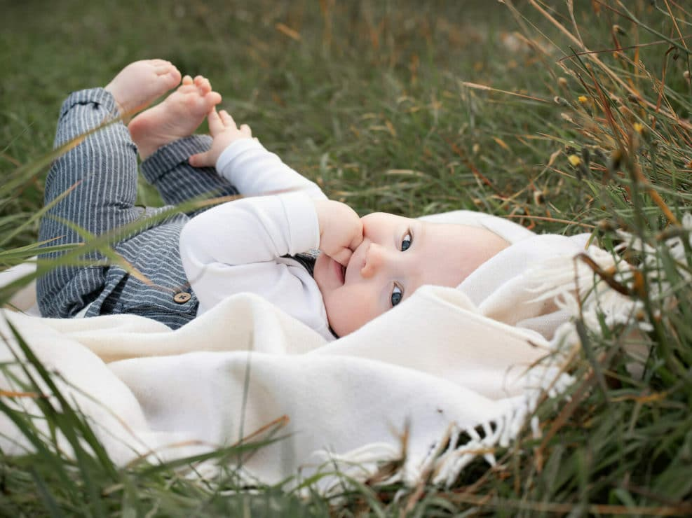 Baby boy lying on grass