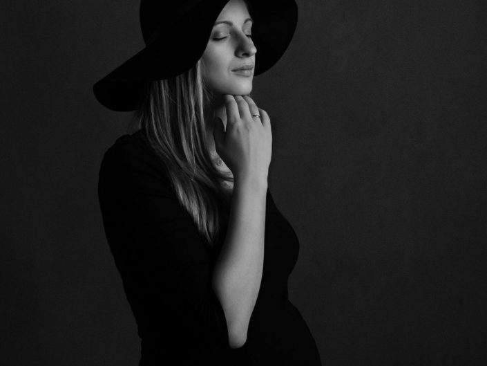 Pregnant woman in black dress and hat on black and white photo