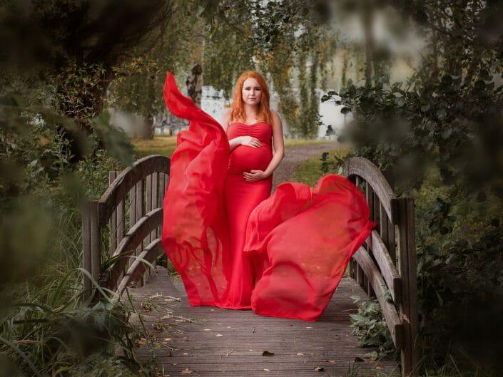 raskaana oleva nainen punaisessa mekossa puistossa