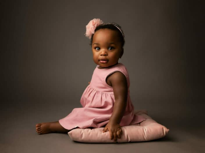 Dark skin one year old girl in a pink outfit sitting on a pink cushion