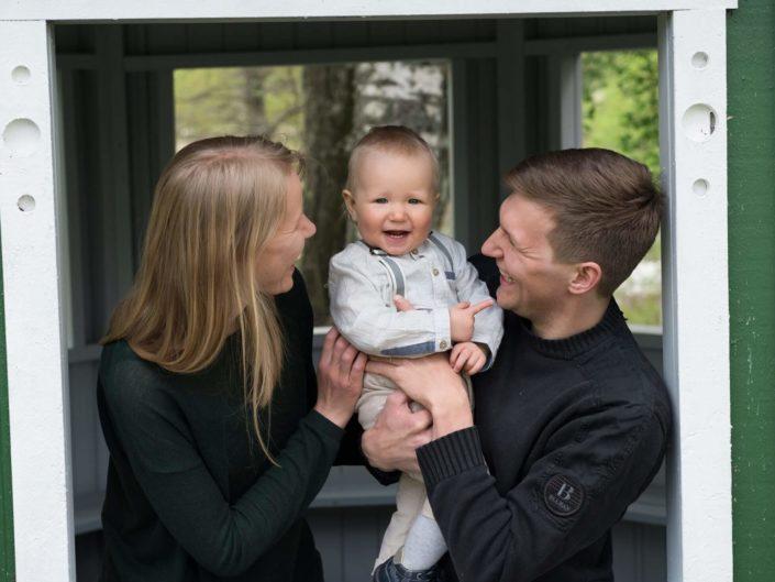 Vanhemmat pojan kanssa kuvauksessa puistossa