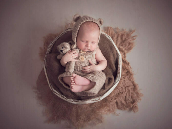 newborn baby in a teddy bear suit holding little bear