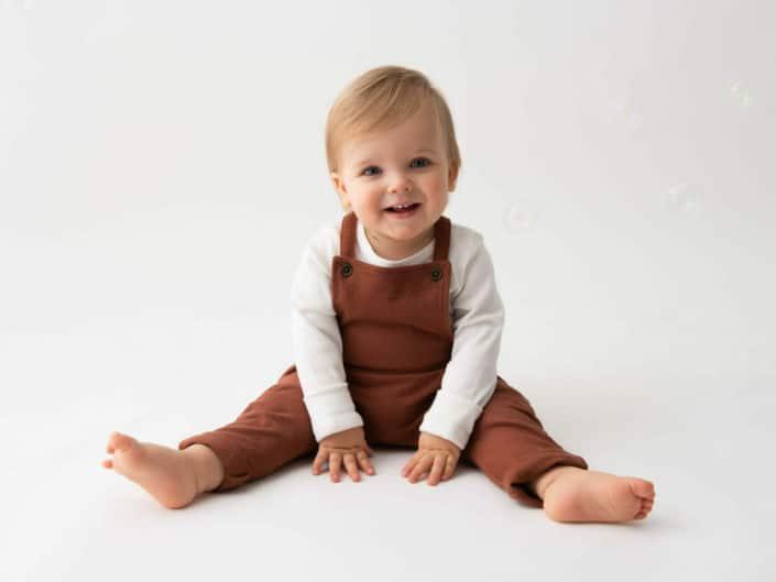 Yksi vuotias poika istumassa lattiassa ruskeassa housuissa