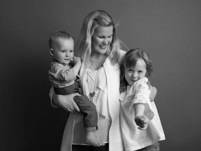 Lapset äidin sylissä perhekuvauksessa