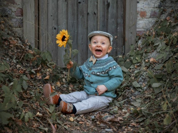 Naurava istuva poikalapsi auringonkukka kädessä lapsikuvauksessa