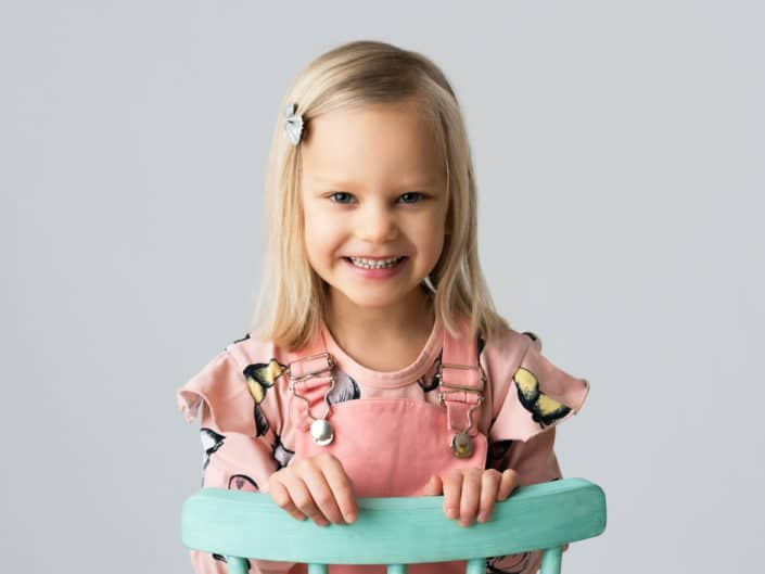 Smiley girl sitting on green chair
